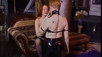 Two leather dominas lick each..