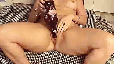 Mature puts a bottle in her fuck hole..
